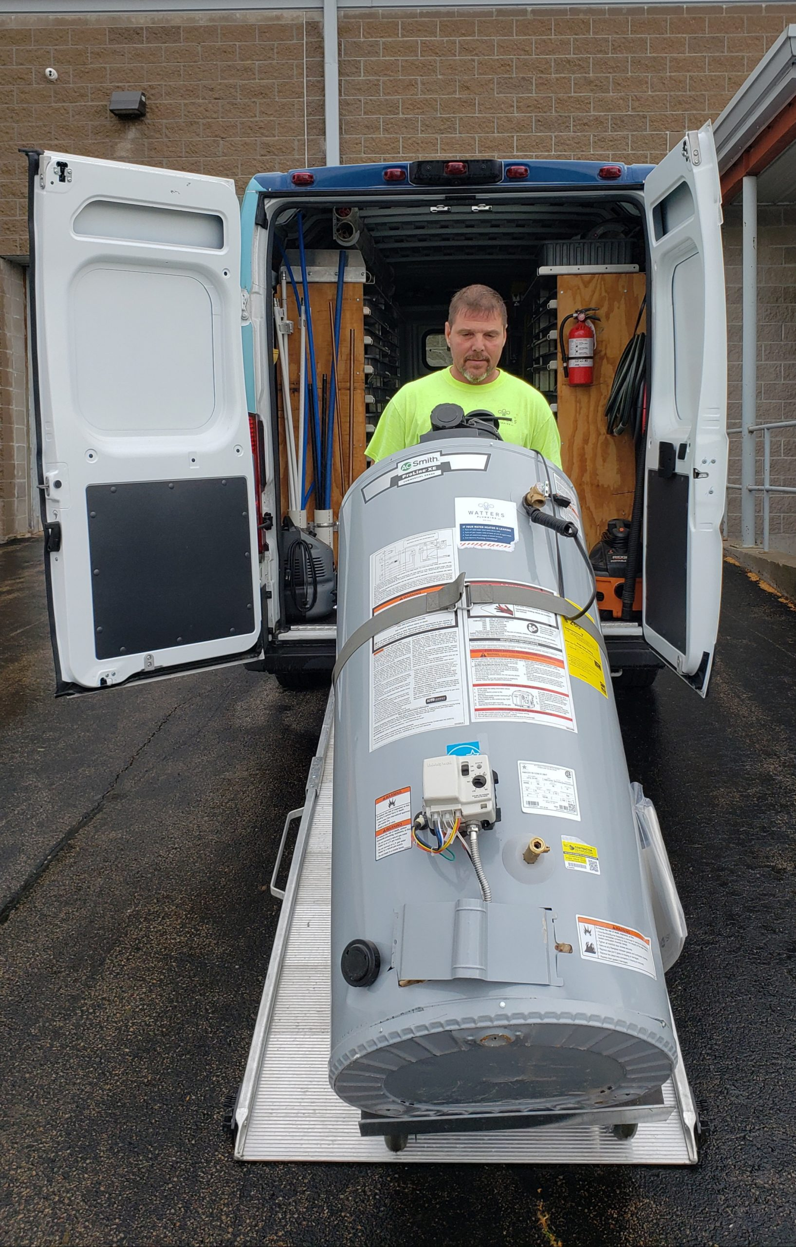 Watters Plumbing's employee loading a water heater into a van for a Northeast Wisconsin home